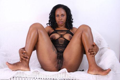 Older black lady sheds her revealing lingerie for nude posing on her bed
